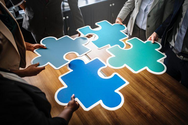 Blaue große Puzzleteile gehalten von einem Team